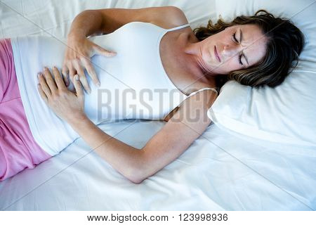 tiredwoman lying in her bed clutching her stomach