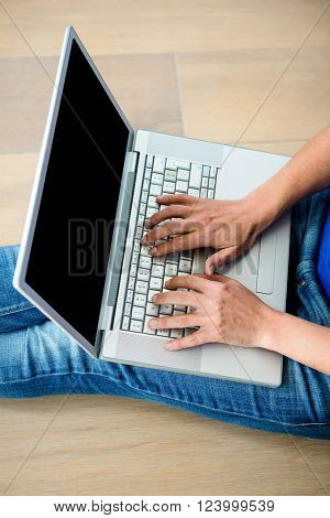 female hands typing on a laptop computer on a wooden background