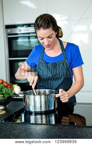 smiling woman cooking vegtables in a saucepan on a stove top