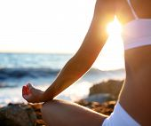 stock photo of mantra  - body of a beautiful girl in a meditation on the beach - JPG