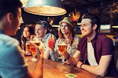 people, leisure, friendship and communication concept - group of happy smiling friends drinking beer poster