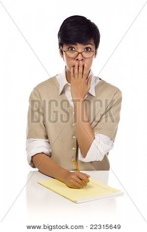 Shocked Mixed Race Young Adult Female Student at Table with Pad of Paper and Pencil Isolated on a White Background.