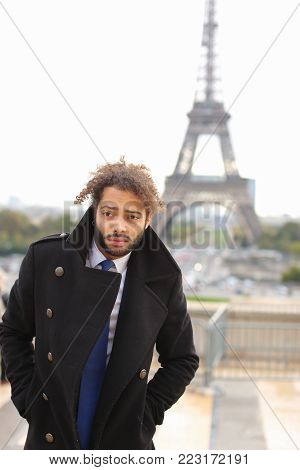 poster of Arabian lovely guy standing around Eiffel Tower for photo session. Young man near Eiffel Tower has fleecy black hair, beard and cute smile. Attractive boy dressed in black coat, white shirt and blue tie. Concept of handsome  dressmakers model with Eiffel