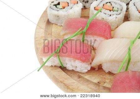 Japanese Cuisine - Maki Roll with Deep Fried Vegetables inside with Set of Nigiri sushi topped with raw Salmon Tuna and Eel. on wooden board . isolated over white background