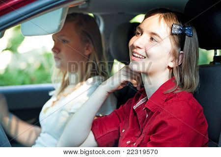 Teen girl is distracted, fixing her hair in the mirror, while driving the car.