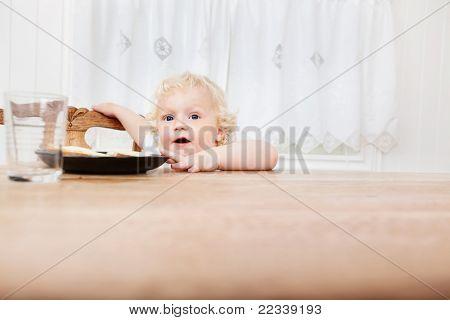 Cute adorable Baby Griff nach Essen auf Tisch