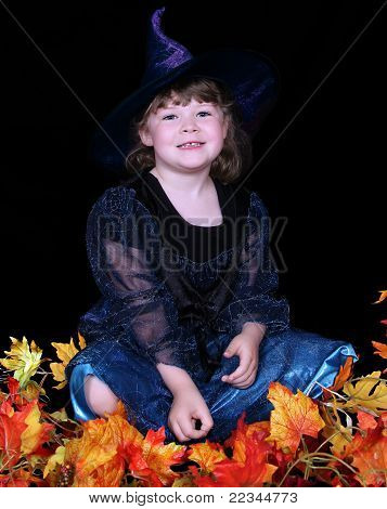 Adorable Little Girl In Witch Costume With Leaves . Isolated