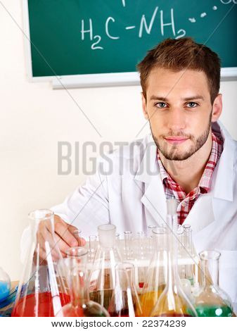Man chemistry student with flask in classroom.