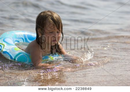 Kid In Buoy Playing With Sand