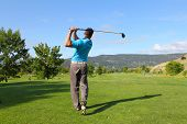 stock photo of young men  - Young male golfer hitting a driver from the tee - JPG