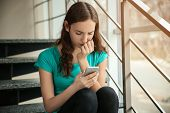Upset teenage girl with smartphone indoors. Cyber bullying poster