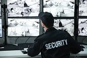 Male security guard working in surveillance room poster