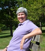 Middle-aged Woman On Bench Smiling