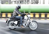 stock photo of riding-crop  - motorbiker rides by industrial estate in Mumbai India Green sewer pipes tarmac road some blur landscape copy space with crop space - JPG