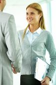 Portrait of happy businesswoman shaking hands with partner at meeting