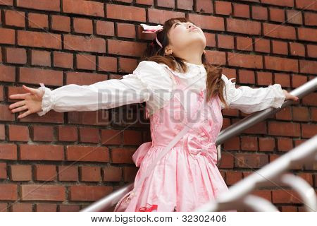 stressed japanese lolita  leaning against brick wall on stairs