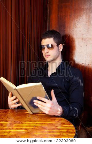 Latin tourist man reading a map book with sunglasses