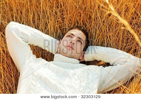 Autumn winter man portrait lying in golden grass field with turtleneck sweater