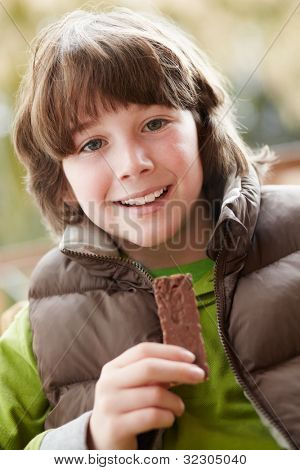 Boy Eating Chocolate Bar Wearing Winter Clothes