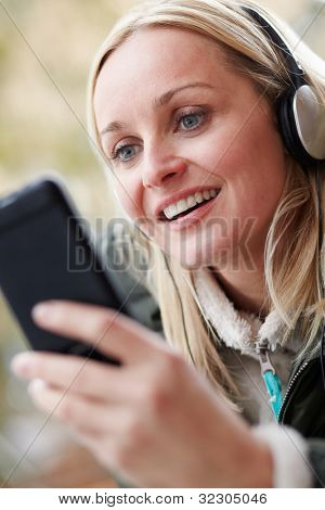 Woman Wearing Headphones And Listening To Music On Smartphone Wearing Winter Clothes
