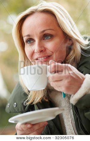 Woman In Outdoor Cafe With Hot Drink  Wearing Winter Clothes