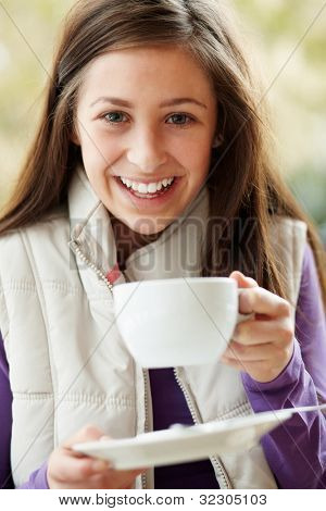 Teenage Girl In Outdoor Cafe With Hot Drink  Wearing Winter Clothes