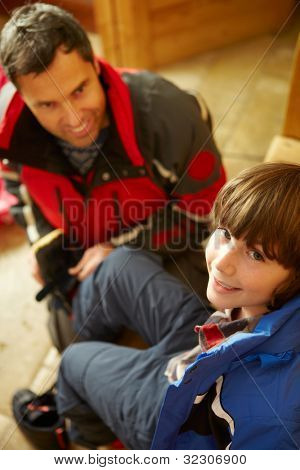 Father Helping Son To Put On Warm Outdoor Clothes And Boots
