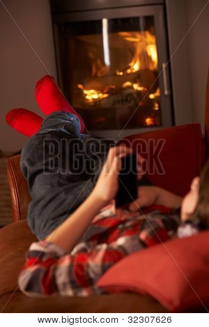 Young Boy Relaxing With MP3 Player By Cosy Log Fire