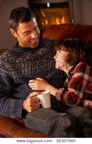 Father And Son Relaxing With Hot Drink By Cosy Log Fire