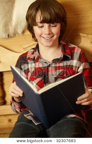 Young Boy Sitting On Wooden Seat Reading Book