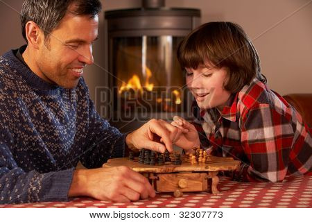 Father And Son Playing Chess By Cosy Log Fire