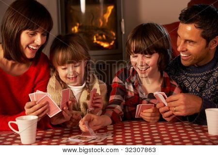 Portrait Of Family Playing Cards By Cosy Log Fire