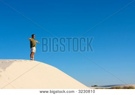 Man Standing Alone On Sand Dune