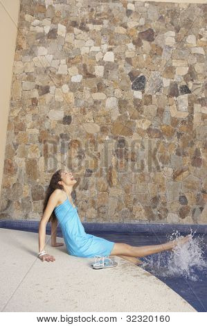 Woman kicking her feet in hotel pool