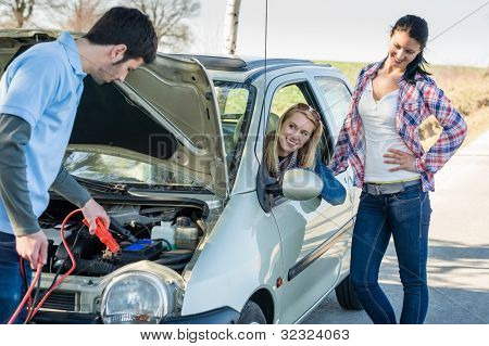 Starter cables man help to repair car two female friends