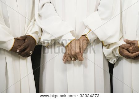 Close up of senior women in choir gowns with hands clasped