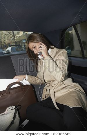 Hispanic businesswoman working in backseat of car