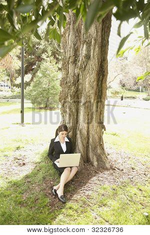 Businesswoman using laptop under tree