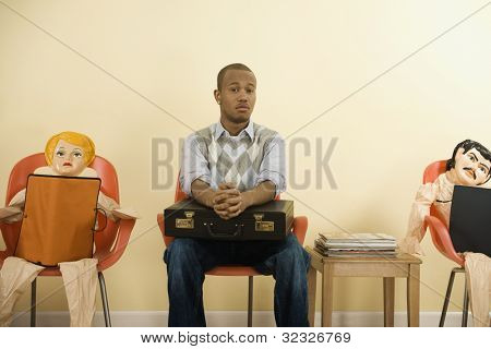 African man with briefcase in waiting area next to blowup dolls