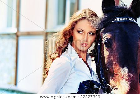 Beautiful young woman with a horse outdoor.
