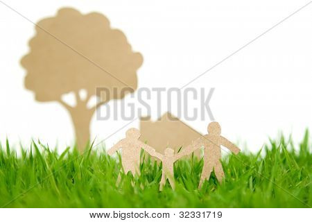 Paper cut of family with house and tree on fresh spring green grass