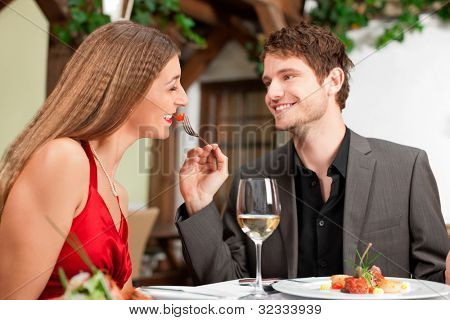 Happy young man feeding woman at the restaurant table