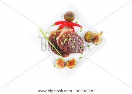 meat entree : grilled beef steak served with red hot cayenne peppers green chives and sweet figs on plate isolated over white background