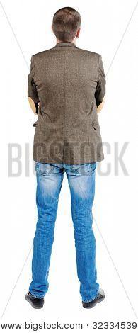 Rückansicht des Geschäftsmann in Jacke. Suchen über sich selbst. stehende junge Mann in Jeans und
