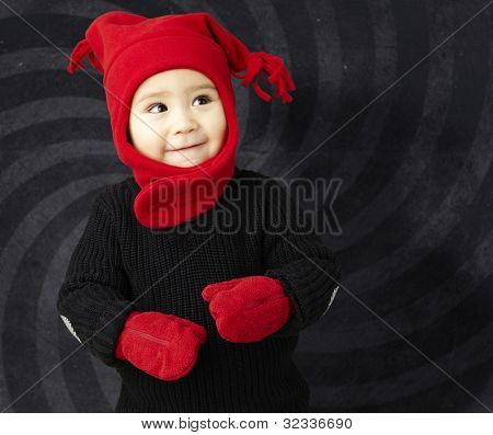 portrait of an adorable kid smiling wearing winter clothes against an abstract background