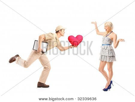 Delivery boy in a rush delivering red heart shaped object and excited woman isolated on white background