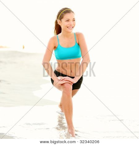 Exercise woman stretching on beach. Fitness sport model smiling happy stretching legs during outdoor work out on sunny summer day. Beautiful mixed race Asian Chinese / Caucasian girl training outside