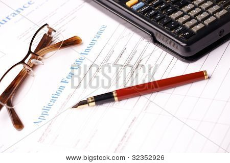 Life insurance application form with fountain pen, glasses and calculator
