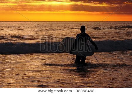 Surfer on the beach at sunset