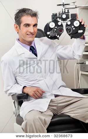 Portrait of male optometrist smiling with phoropter at his clinic
